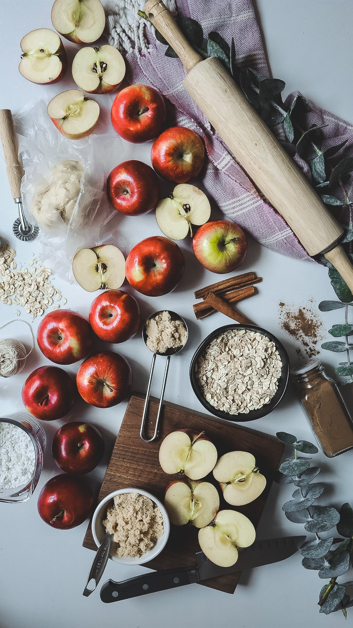 red apples, baking ingredients , a rolling bin and oats all styled on a counter top