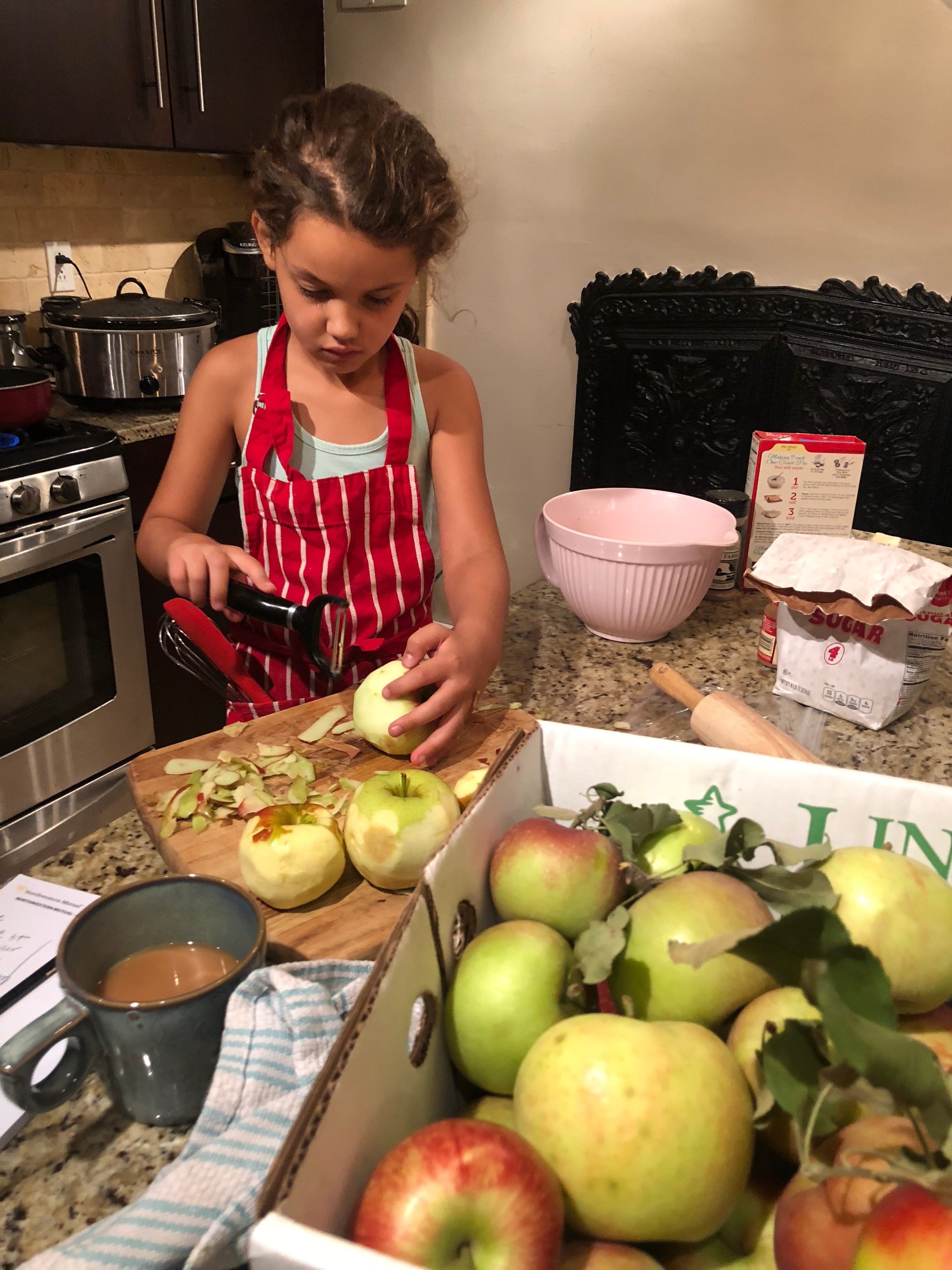 A little girl in a red apron is peeling apples