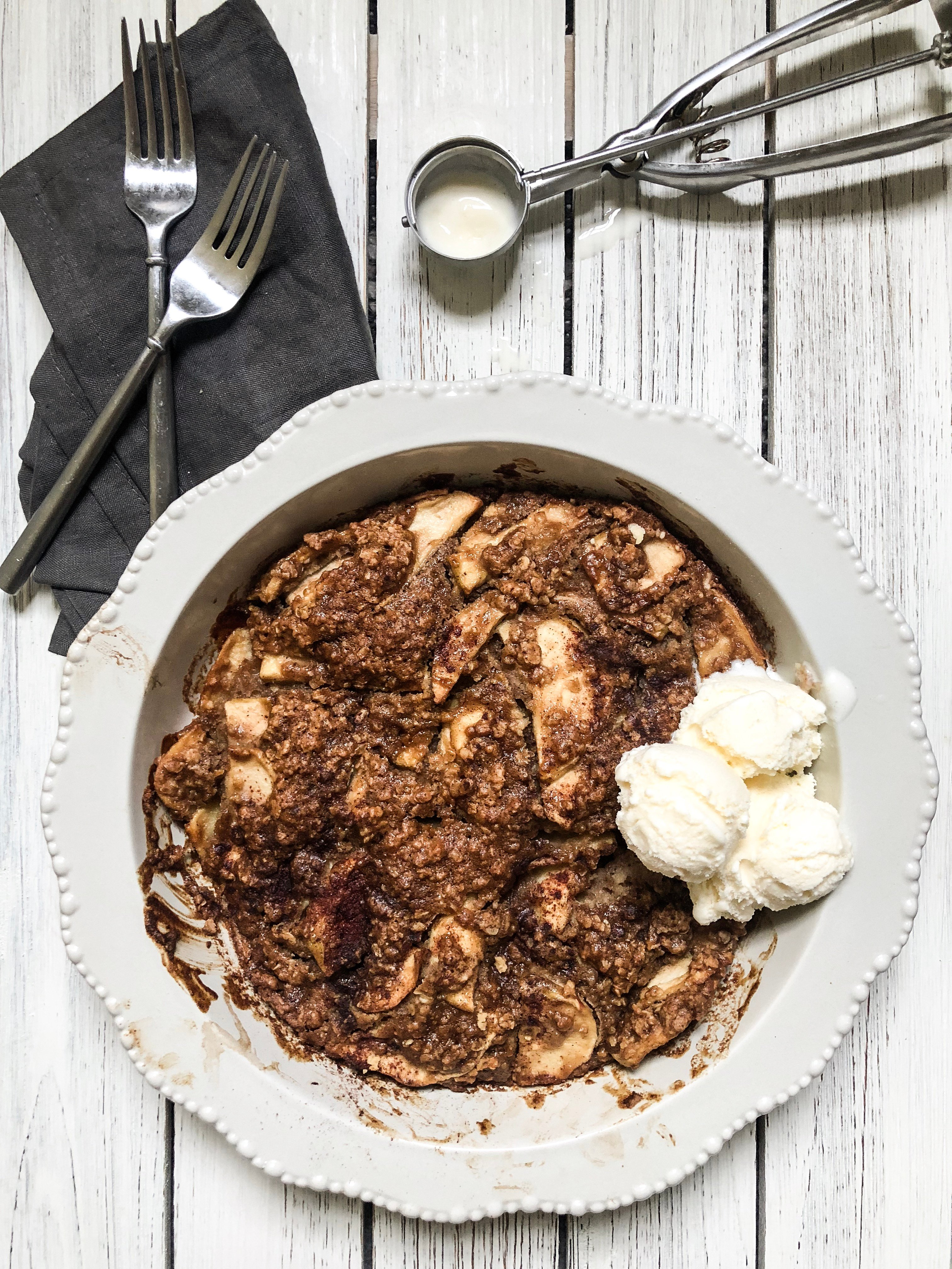 a pie plate filled with Apple Crisp with crunchy topping and ice cream, forks and spoons.