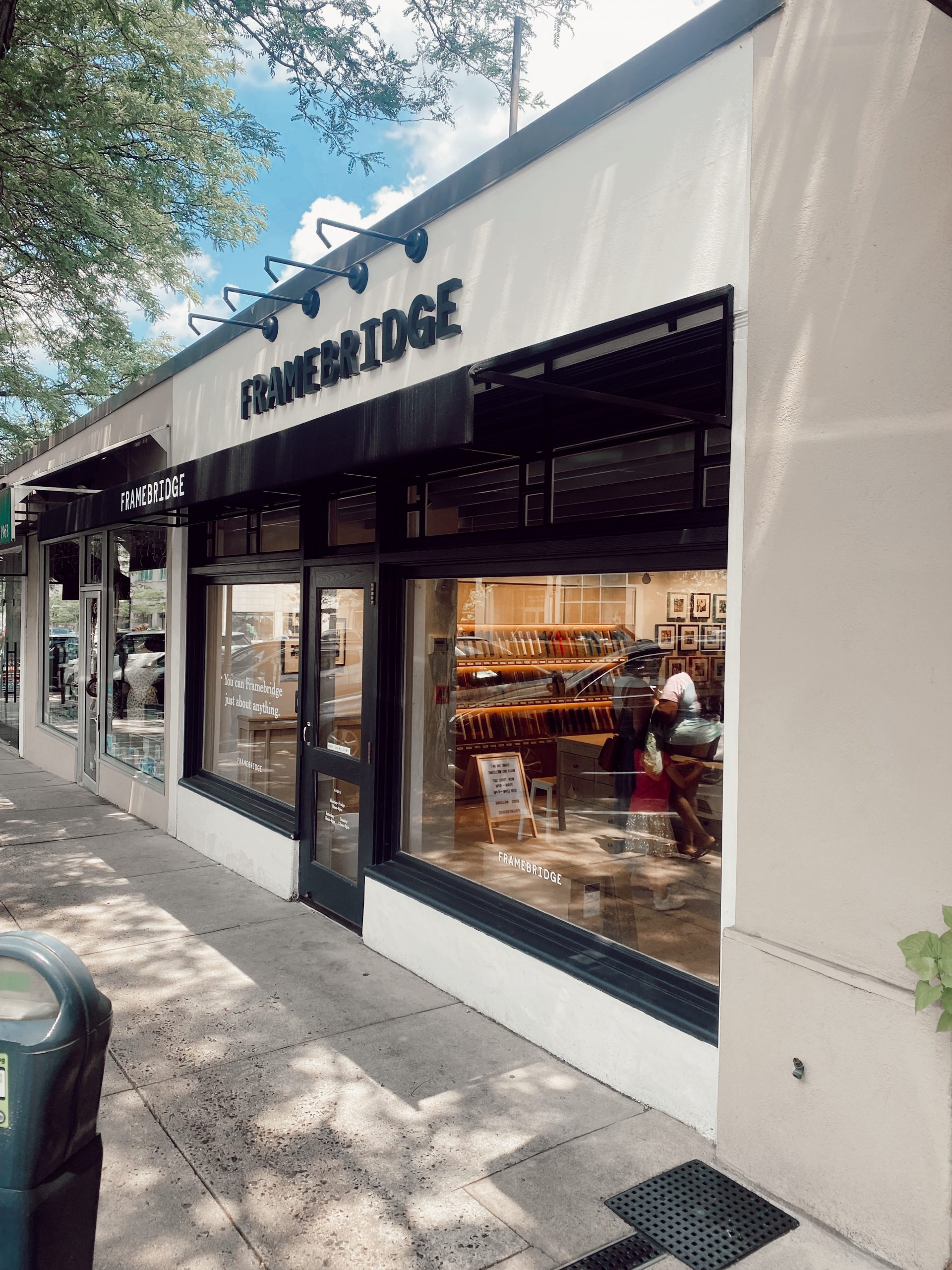 The store exterior of the Framebridge Store at Suburban Square in Ardmore PA is brightly lit with colorful frames and artwork.