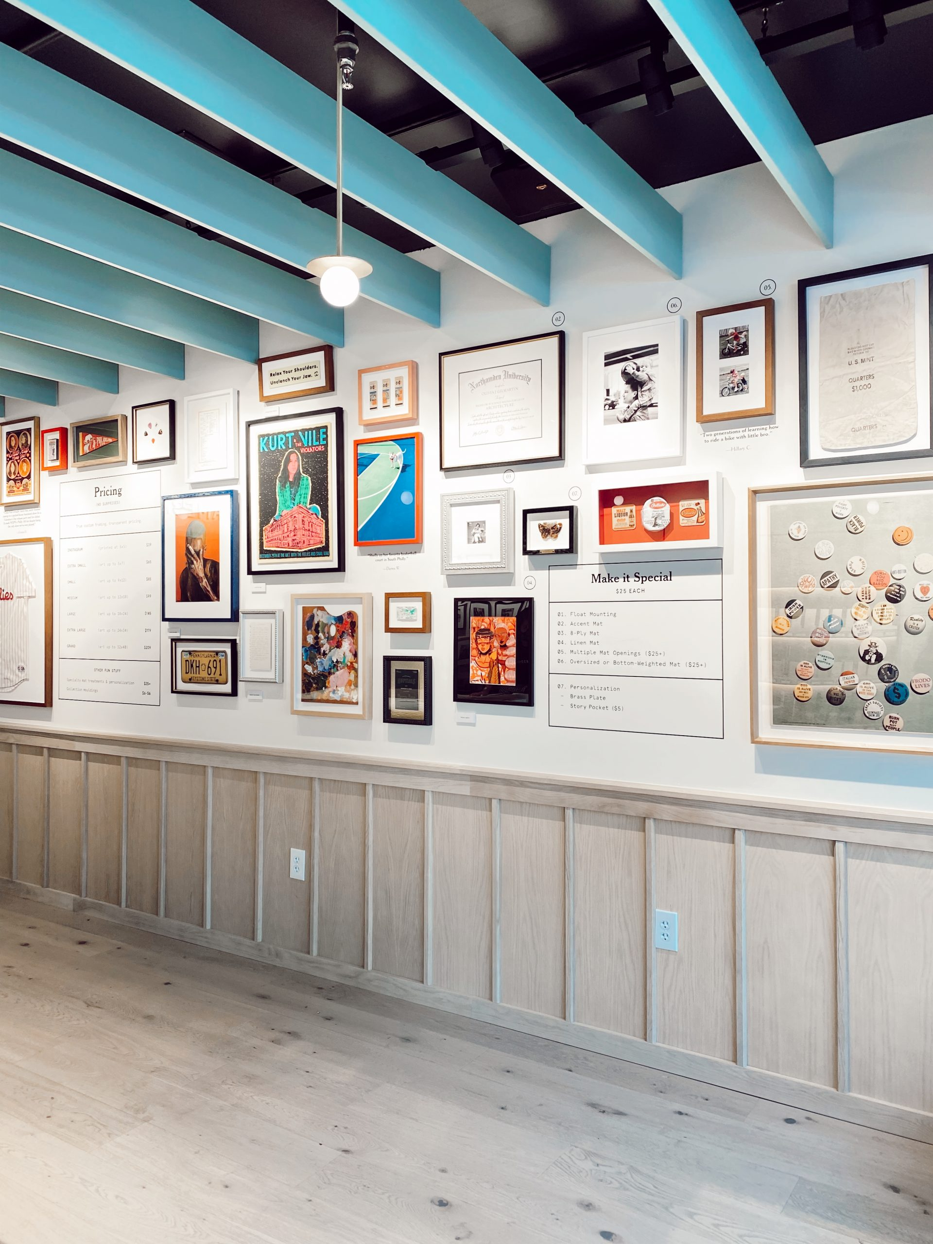 inside the Framebridge Store with brightly colored frames in a gallery on the wall.