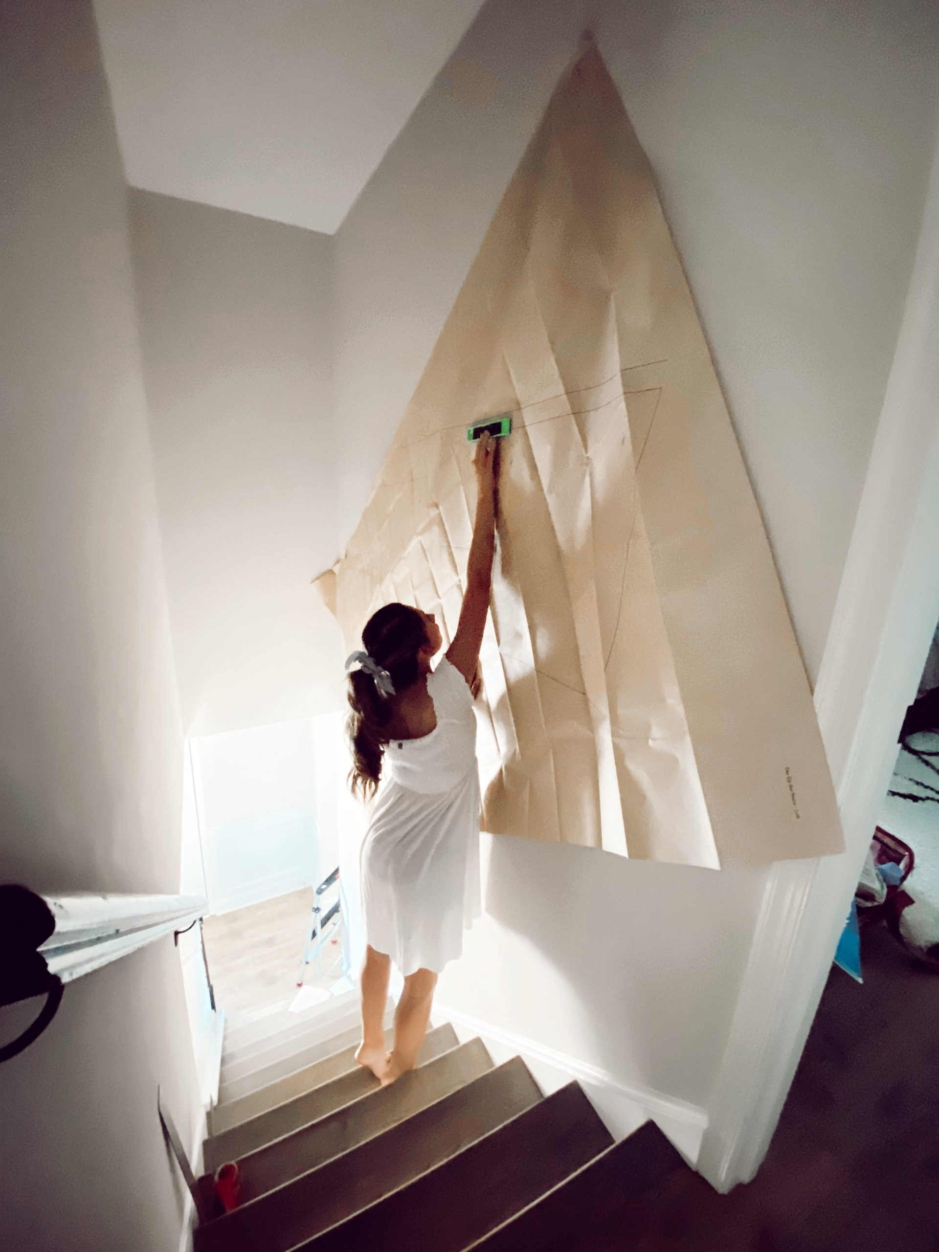 a woman installs a frame bridge gallery wall on the staircase
