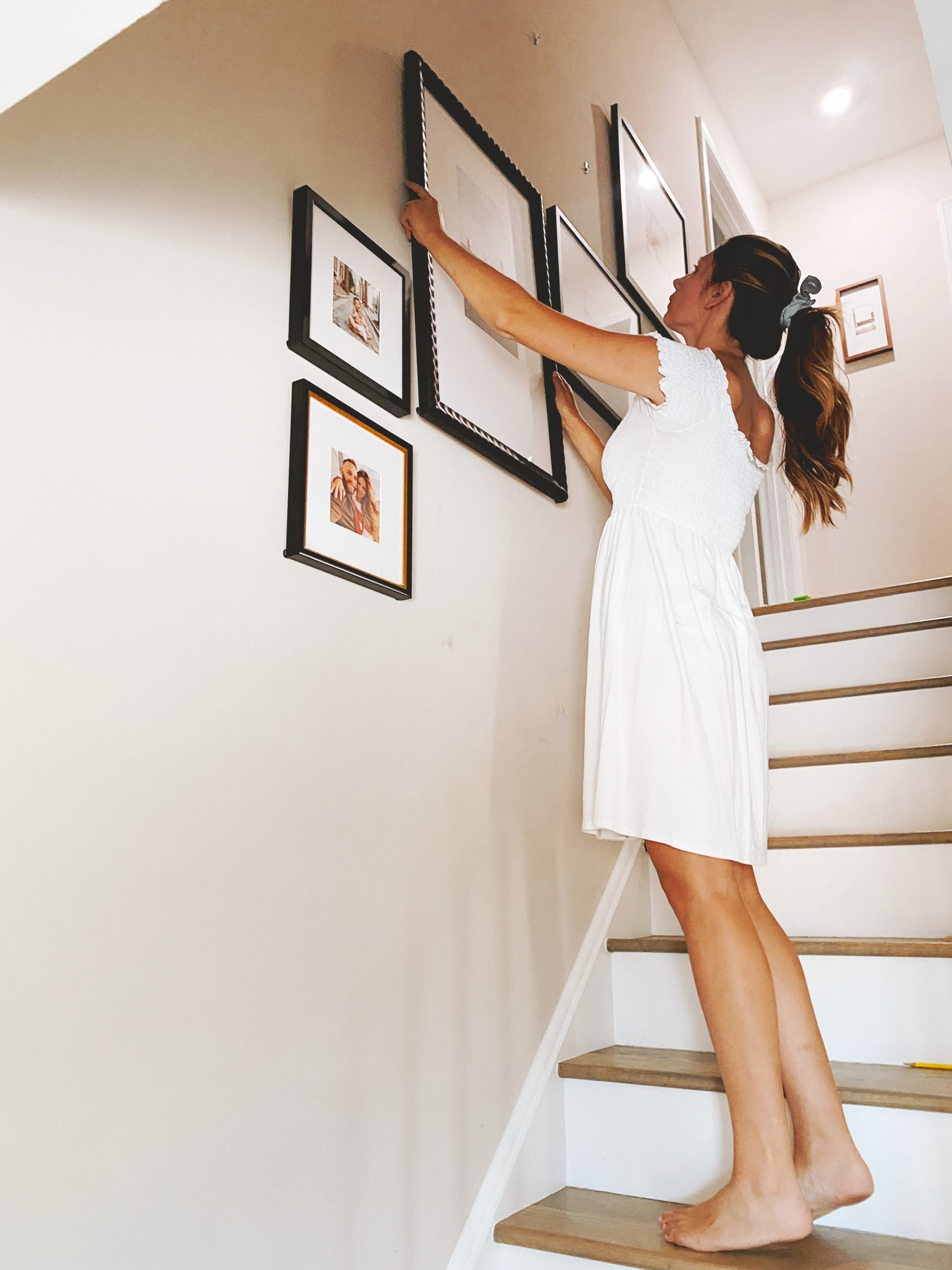a woman in a white dress hangs photos in a gallery wall on a staircase