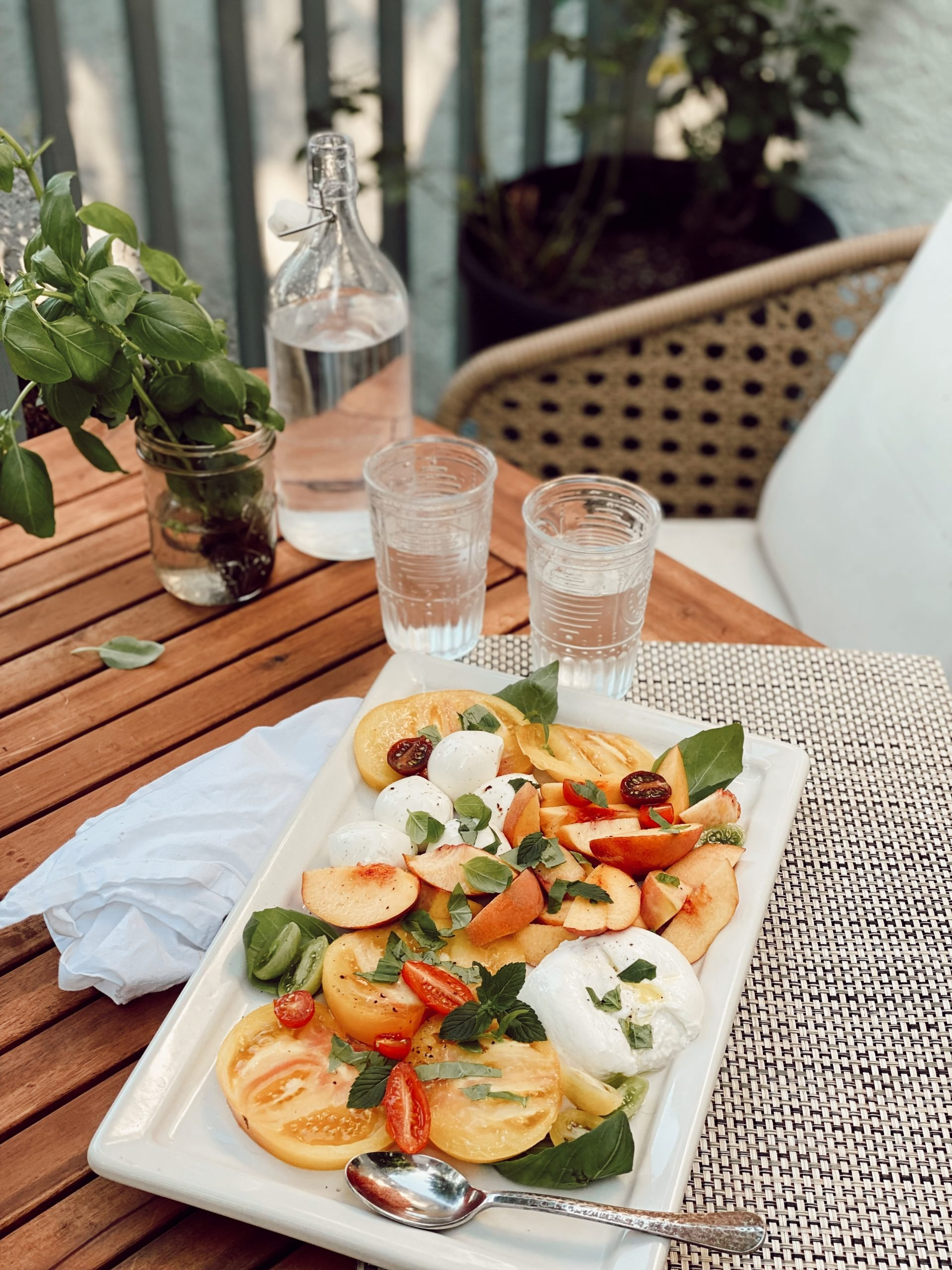 a colorful salad of burrata, tomatoes and basil on top of a wooden table with clear glasses and water
