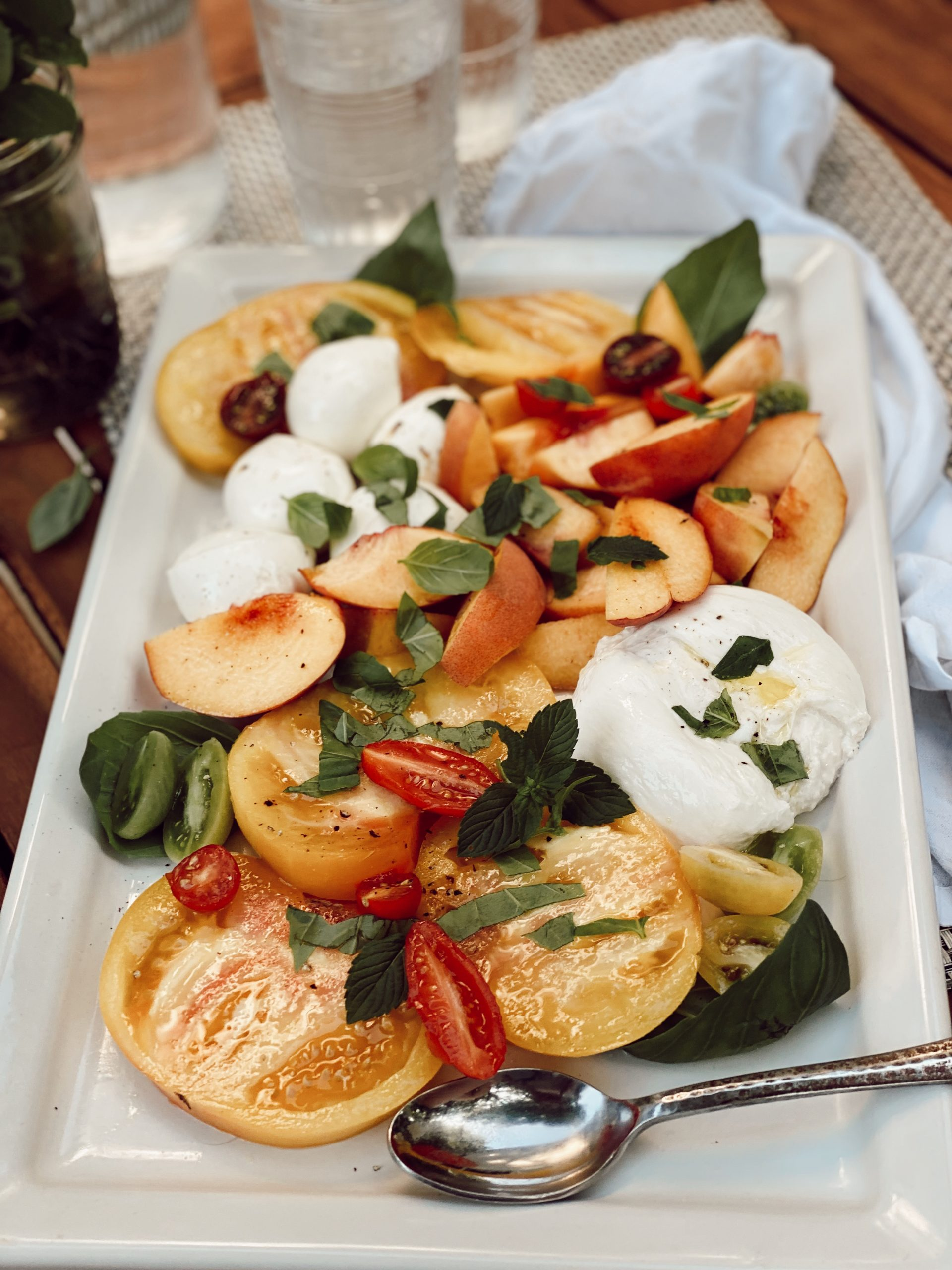 colorful salad with burrata, tomatoes, peaches and basil