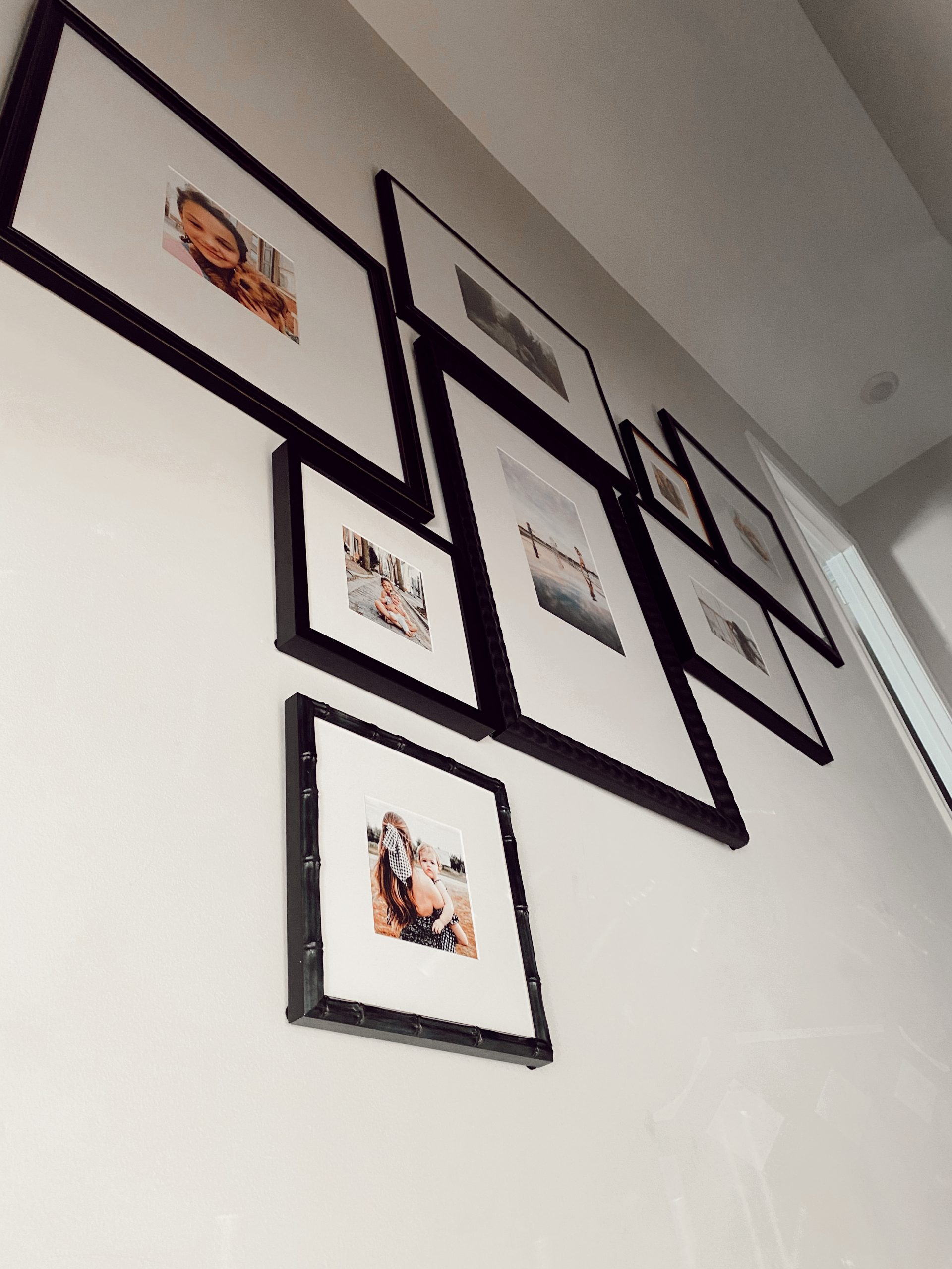 a Framebridge Gallery Wall of black frames going up the stairs