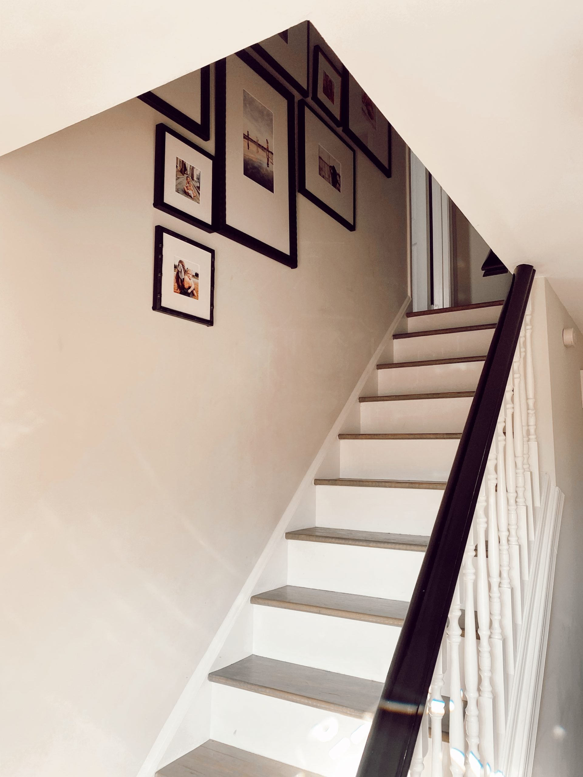A staircase with white walls and a Framebridge Gallery Wall going up the stairs