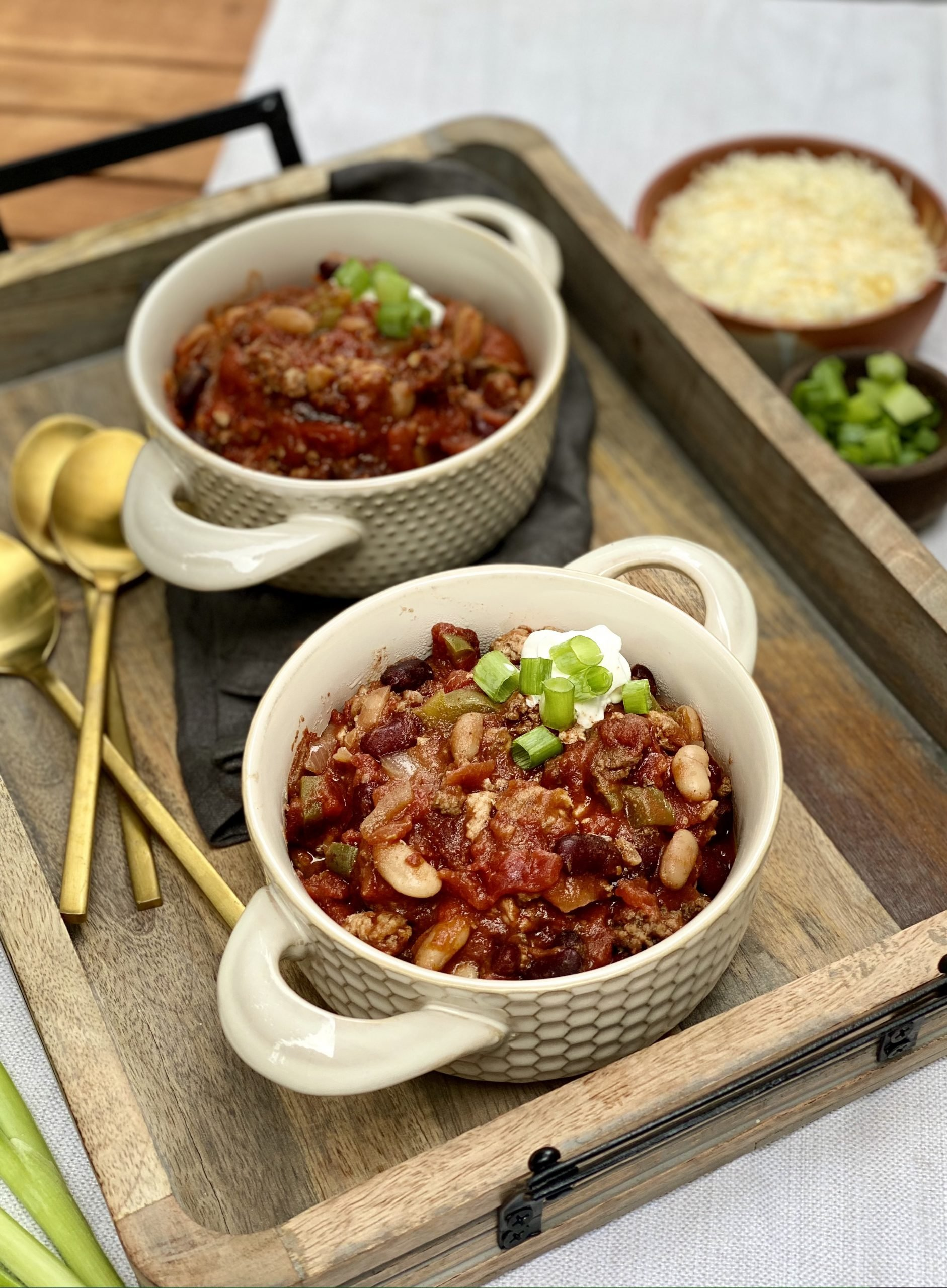 two bowls with chili with beans and ground beef garnished with cheese and green onions.