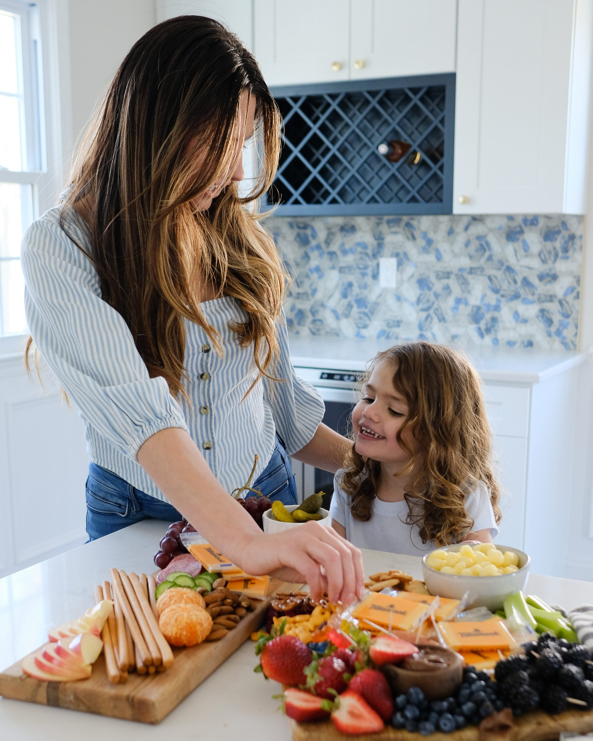 a woman and her daughter both with long brown hair eating from a snack board