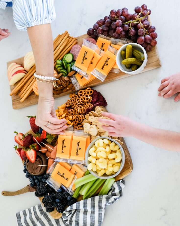 a snack board with popcorn, cheese, apples and snacks for kids with kids hands in the photo