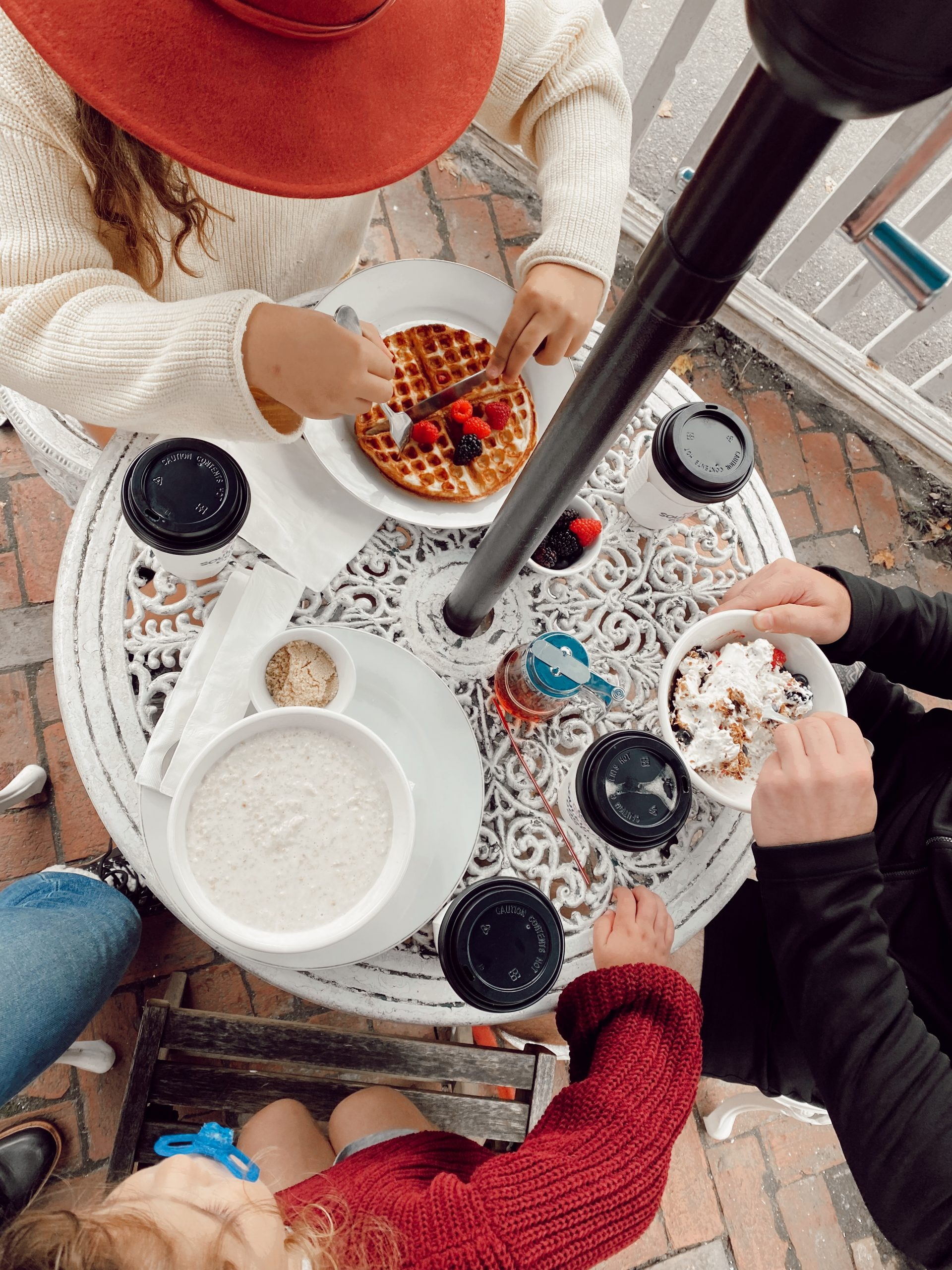 a family eating breakfast of waffles and oatmeal over a white table