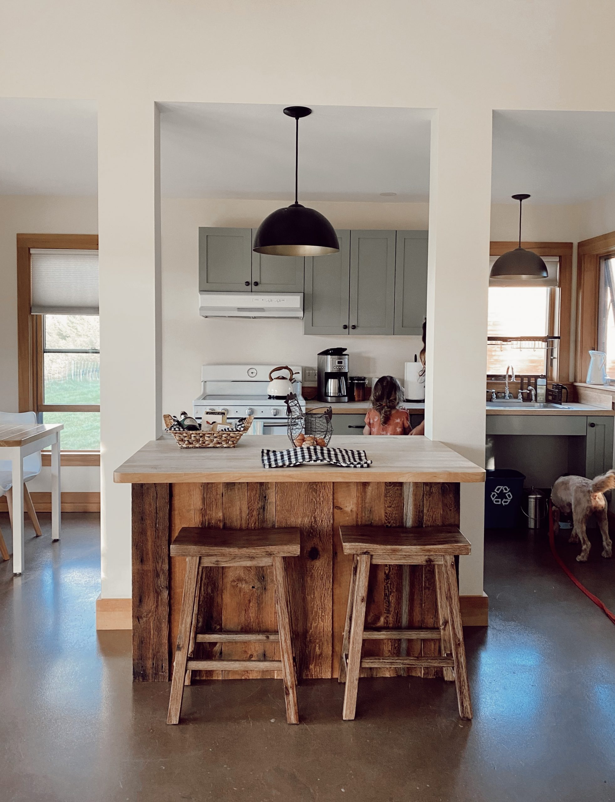 a cabin kitchen with wooden counter tops, stools and green cabinetry