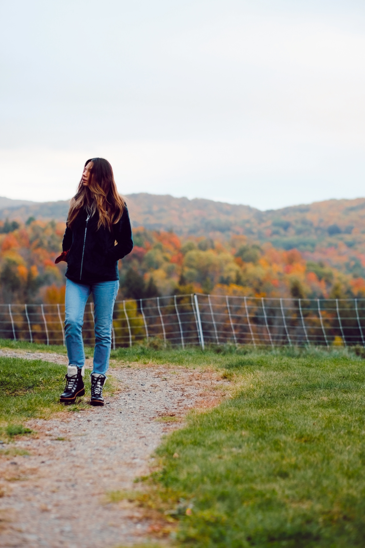 a woman walking in hiking boots, jeans and long brown hair hiking in the fall